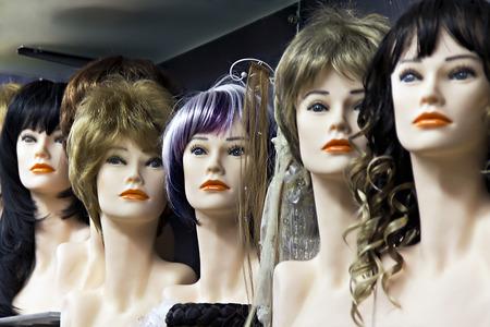 Verschillende vrouwelijke mannequins met pruiken op de plank
