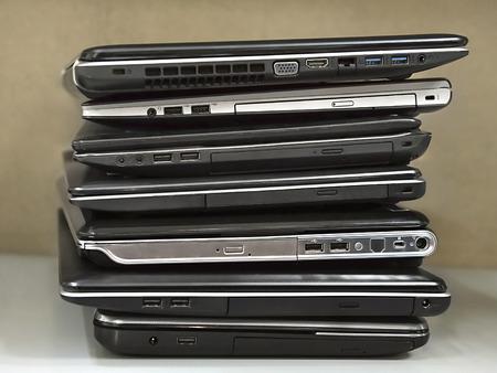 awaiting: stack of old laptops awaiting repair Stock Photo