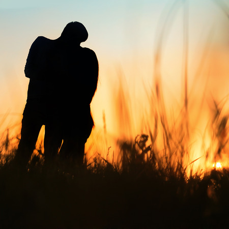 female silhouette: silhouette of a young couple kissing at sunset