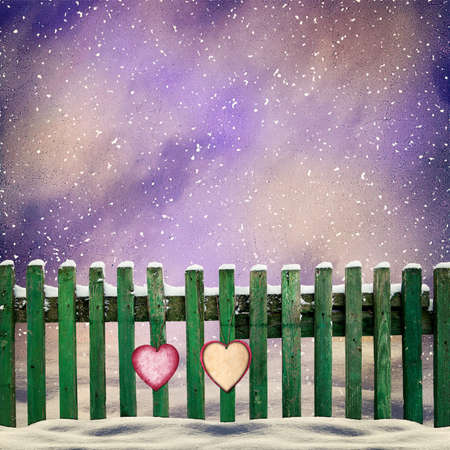 snowcovered: snow-covered wooden fence with two paper hearts Stock Photo