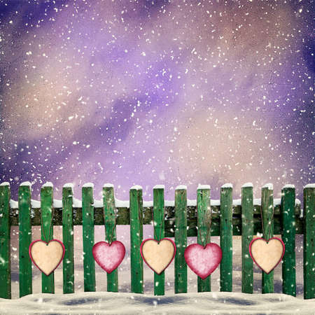 snowcovered: snow-covered wooden fence with hanging on it with paper hearts