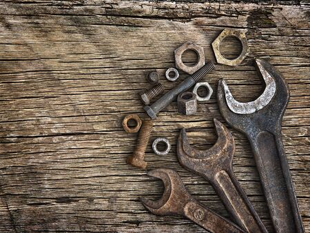Old wrenches on the nuts and bolts on a wooden grungy background photo