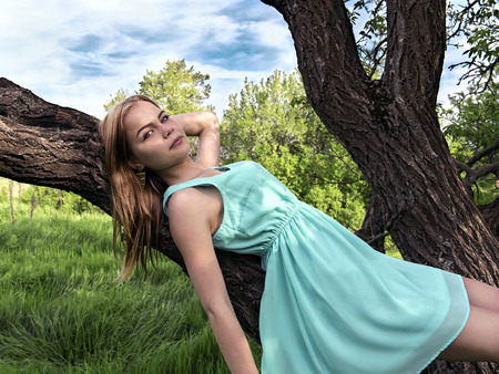 Young sensual blonde girl lying on a tree branch photo