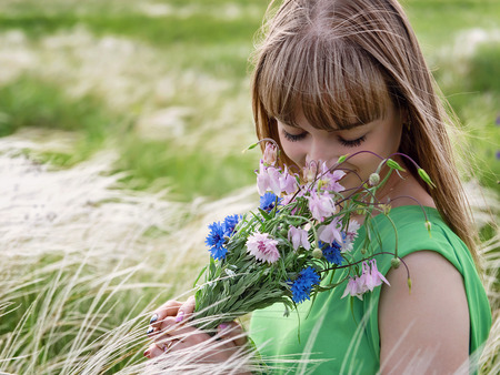 Young sensual girl smelling a bouquet of wildflowers photo