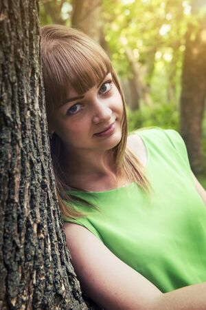 young tree: Young sensual girl leaning against a tree Stock Photo