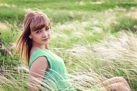 Young sensual girl sits in a grass outdoors Stock Photo