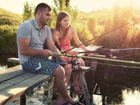 Jong gezin visvakantie met houten planked voetpad