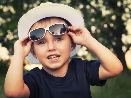 ni�os rubios: Retrato de un ni�o alegre en gafas de sol Foto de archivo