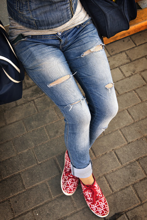girl in ripped jeans sitting on the bench