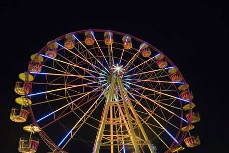 the backlighting: Ferris wheel with lights backlighting the night sky