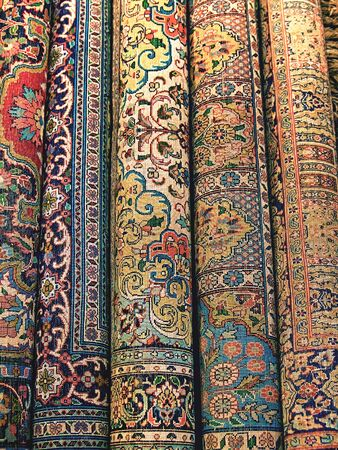 Indian carpets are rolled into rolls as background