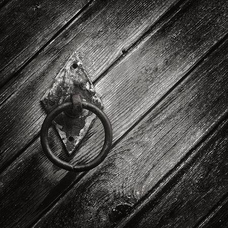 vintage circular iron doorknob on the door of the old wood planks