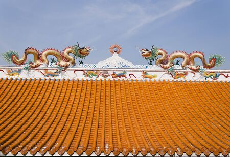 twin dragon on the roof of shrine with blue sky background photo
