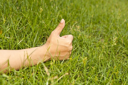 Hand finger good on green grass . Stock Photo