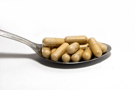 The ancient herbal capsule in spoon Stock Photo