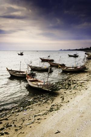 barco de pesca de madera, mar de fondo y el cielo del atardecer