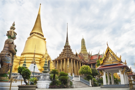 Golden pagoda of Wat Phra Kaew thailand with green photo