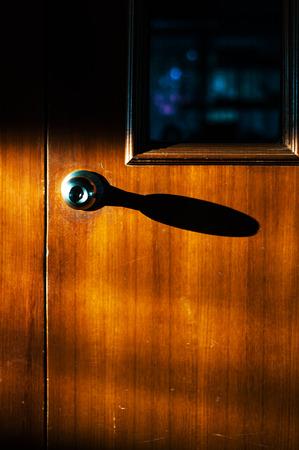 Antique door knob on a wooden door photo