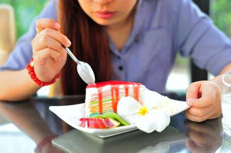 An Womenl eating fancy cake in soft light .