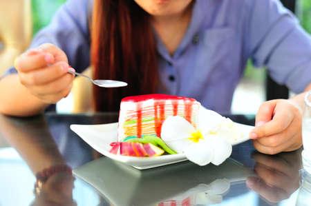 fancy cake: An Womenl eating fancy cake in soft light .