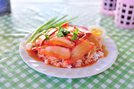 An thai food is name rice red pork sauce .