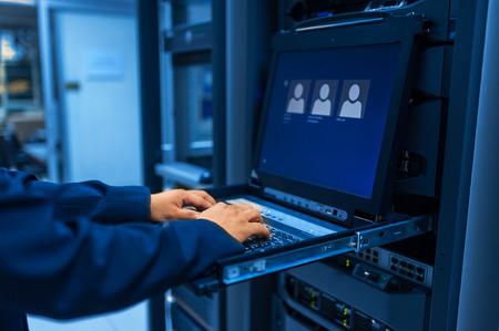 Człowiek naprawić sieć serwerów w centrum danych w pokoju. Zdjęcie Seryjne