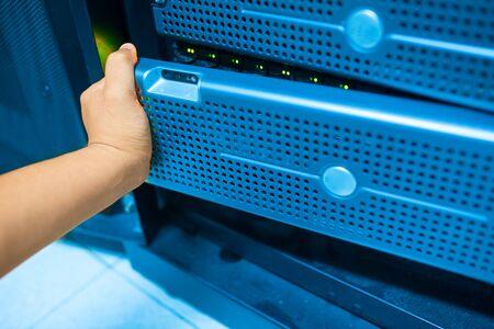 network server: Man fix server network in data center room .