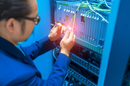 People fix node fiber optic in network room .