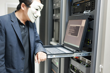 Masked Hacker in Computer Server room Concept . Stock Photo