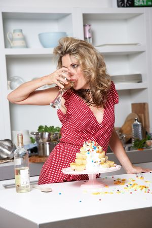 domestic kitchen: woman in a red dress cooking in a kitchen