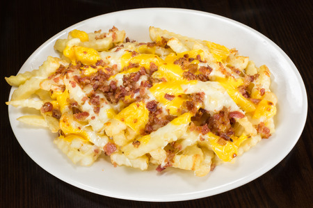 Disco Fries - French fries topped with melted yellow cheddar cheese and sprinkled with bits of bacon, arranged on a white plate