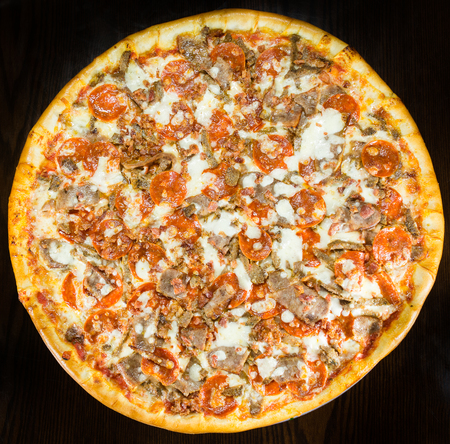 unsliced: Large pizza topped with Italian sausage, pepperoni, bits of bacon and mozzarella cheese, whole unsliced pie