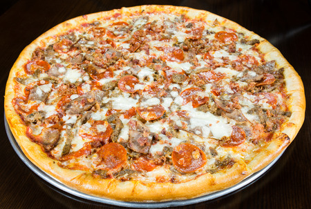 unsliced: Large pizza topped with Italian sausage, pepperoni, bits of bacon and mozzarella cheese, whole unsliced pie on a metal platter Stock Photo