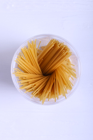 Multicolored pasta with the addition of natural vegetable dye. In jar on a white table. Top view, copy Space.