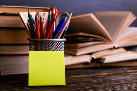 Notebook, open books and stand for pens on dark wooden table on the background of chalk board. Learning knowledge at school, sticker copy space.