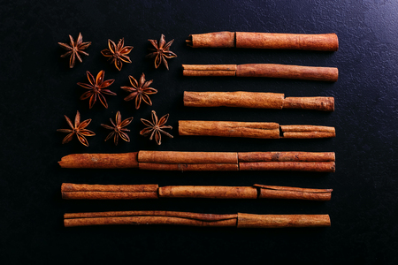 Badian and cinnamon in the shape of the American flag. Fragrant spices for coffee drink, close-up, concept americano.