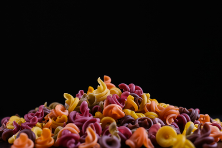 Multicolored pasta with the addition of natural vegetable dye. They lie in a pile on black background. 写真素材