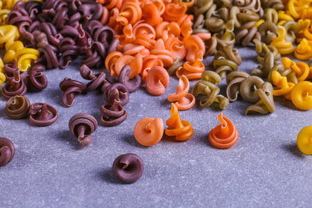 Multicolored pasta of unusual shape with natural vegetable dyes, scattered on table. Background closeup. 스톡 콘텐츠