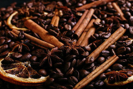 Cinnamon sticks, star anise, coffee beans and dried orange on kitchen table. Fragrant spices for coffee drink, close-up.