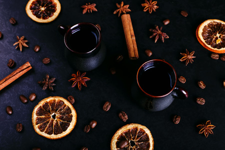 A cup of coffee, star anise, cinnamon, dried orange and coffee beans on a dark kitchen counter top.