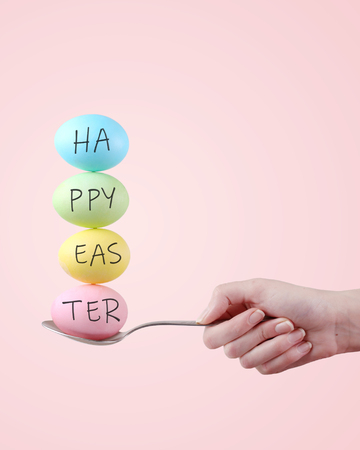Female hand holds a spoon on which multi-colored eggs are balanced, on pink background. Unusual design, Easter concept, copy space.