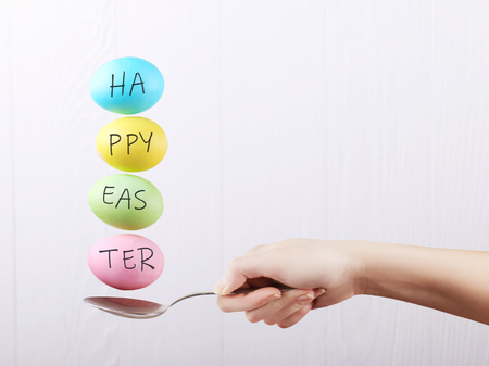 Female hand holds a spoon on which multi-colored eggs are balanced, on white background. Unusual design, Easter concept, copy space.