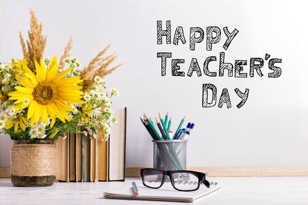 Bouquet of flowers and notebooks with eyeglasses on table. The inscription happy teachers day.. Stock Photo