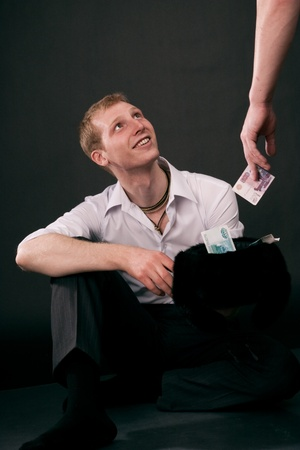 denominations: Adult guy takes money on black background