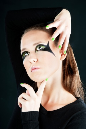 Close-up portrait of beautiful brunette with green eye shadow mask photo