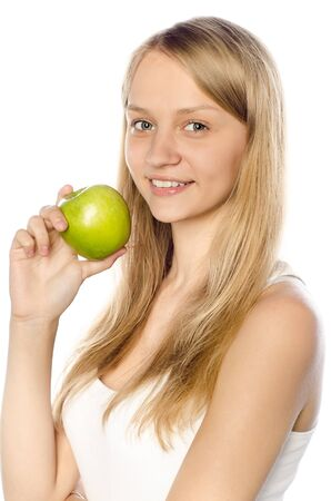 Gorgeous young woman holding a green apple in her hand against white background photo