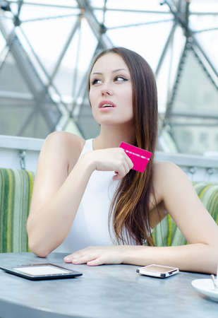 Closeup portrait of a pretty young female holding credit card  photo