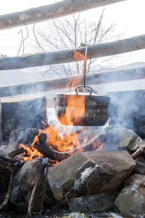 boiling pot: Cooking in field conditions, boiling pot at the campfire on picnic, mountains,