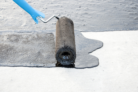 ruberoid: Roofer worker painting  bitumen praimer at concrete surface by the roller brush,   for waterproofing.