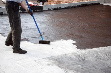 屋根葺き職人労働者絵画アスファルト praimer 防水用ローラーのブラシによるコンクリート表面で。 写真素材 - 50297374